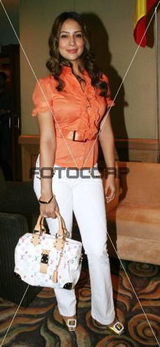 kim-sharma-white-pants-orange-top.jpg